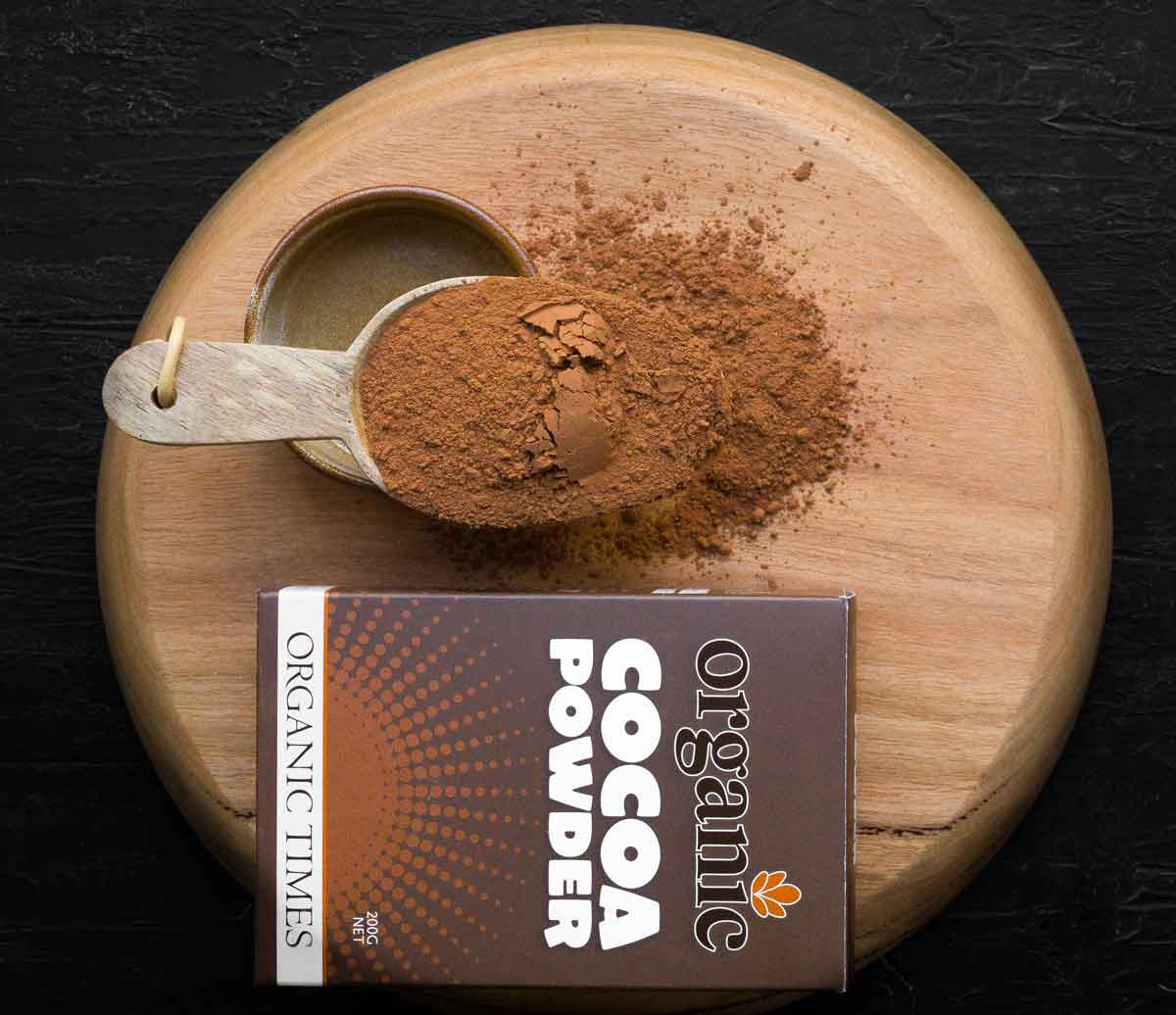 A spoon of Organic Times Cocoa Powder with packaging on the side